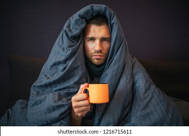 Picture of young man sits on bed and covered up with dark blue blanket. He holds orange cup of tea. Guy looks on camera. He is serious. Young man is emotionless.