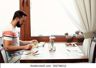 Picture of young man sitting alone at hotel restaurant table and eating breakfast