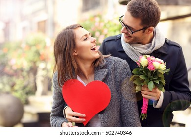 Picture of young man surprising woman with flowers and heart
