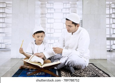 Picture of young man wearing Islamic clothes while teaching his son reads the Quran in the mosque