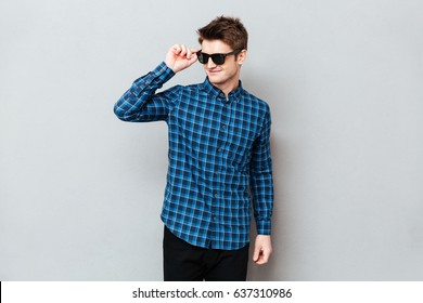 Picture of young man wearing sunglasses standing over grey wall and looking aside.