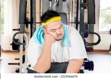 Picture of young obese man looks lazy while sleeping on the exercise machine. Shot in the gym center