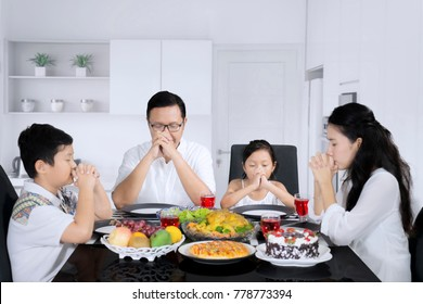 Picture of young parents with their children praying before meals while sitting in the kitchen