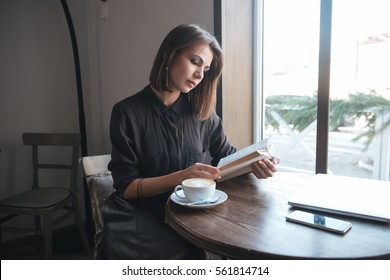 Picture of young pretty woman sitting at the table in cafe and reading book.