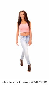 A picture of a young pretty woman standing in jeans and a pink top, in full lengths, isolated on white background.
