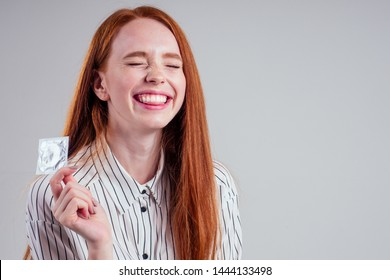 picture of young redhead be lost in thought businesswoman in striped shirt with pack of condom and birth choosing thinking white background studio