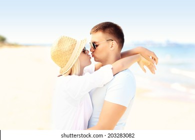 A picture of a young romantic couple kissing at the beach