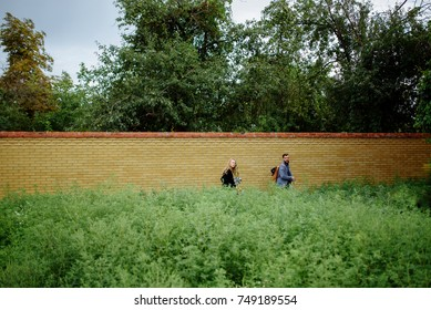 A picture of a young romantic couple neat the wall in garden