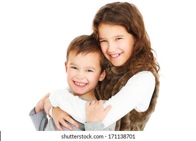 A picture of young siblings hugging over white background