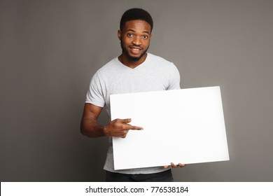 Picture of young smiling african-american man holding white blank board and pointing on it, on grey background, copy space