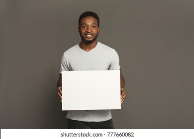 Picture of young smiling african-american man holding white blank board on grey background, copy space