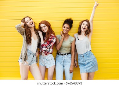 Picture of young smiling women friends standing over yellow wall. Looking at camera.