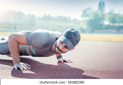 Picture of a young sportsman doing push ups outdoors, fitness and exercising in the park. Sport, recreation, lifestyle concept