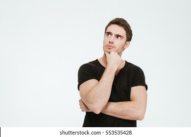 Picture of young thoughtful man dressed in black t-shirt standing over white background looking aside.