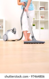 A picture of a young wife hoovering her apartment