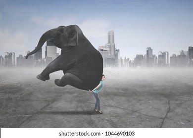Picture of young woman carrying an elephant while standing with modern city background