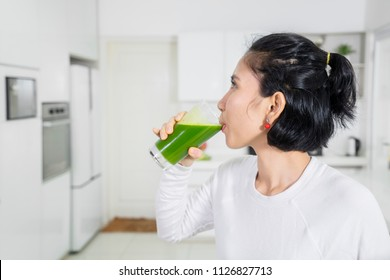 Picture of young woman drinking healthy juice while standing in the kitchen
