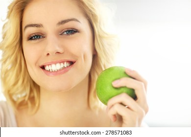 A picture of a young woman eating an apple at home