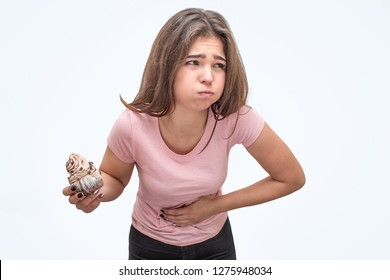 Picture of young woman hold eclair. She is going to puke. Model hold hand on stomach. She feels bad. Isolated on white background.