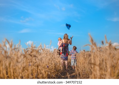 Picture of young woman holding baby standing with boy in wheat field. Backview of happy family having fun on summer countryside background.