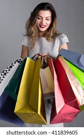 Picture of a young woman looking at colorful shopping bags