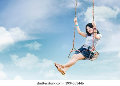 Picture of young woman looks happy while sitting on the swing with blue sky background