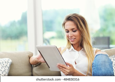Picture of young woman on couch with tablet