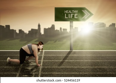 Picture of young woman preparing for running with healthy life text at signpost