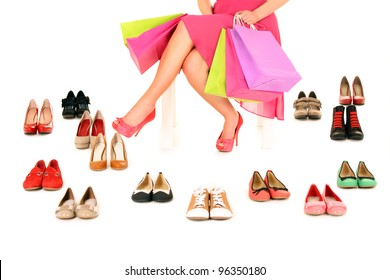 A picture of a young woman sitting with shopping bags among shoes over white background