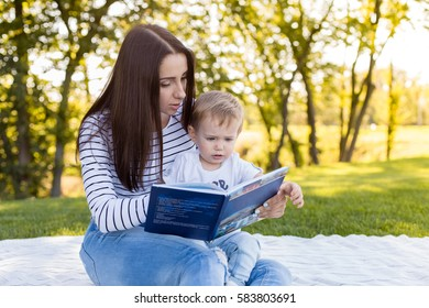 Picture of young woman with son sitting down on green grass field and read fairytale in park.