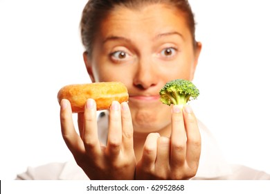 A picture of a young woman trying to decide between healthy and unhealthy food