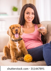 Picture of young woman is watching tv while her dog is lying on sofa near her.