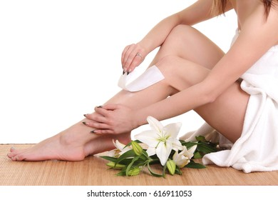 A picture of a young woman waxing her legs over white background
