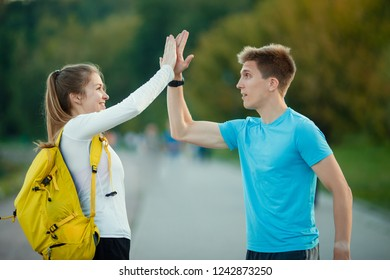 Picture of young women and men doing handshake in park on summer day.