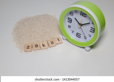 A picture of zakat word tiles, rice and clock with copyspace. Time of Zakat Al Fitr is going to end this year.