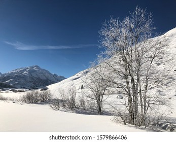 A picture-perfect deep snow morning on the Nordic ski track in Andermatt. Clear blue sky, very cold, snow-covered trees and mountains. Winter sport perfection.