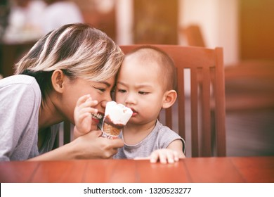 Pictures of Asian women eating ice cream with her son In a happy mood. Focus on the mother's face.
