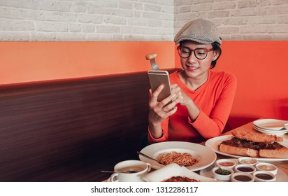 Pictures of Asian women who are eating and using her mobile phone at the same time happily.Focus on face