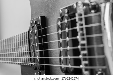 Pictures of a black and white electric guitar. Strings and bridge. Wooden body of the guitar Music equipment. Metal strings