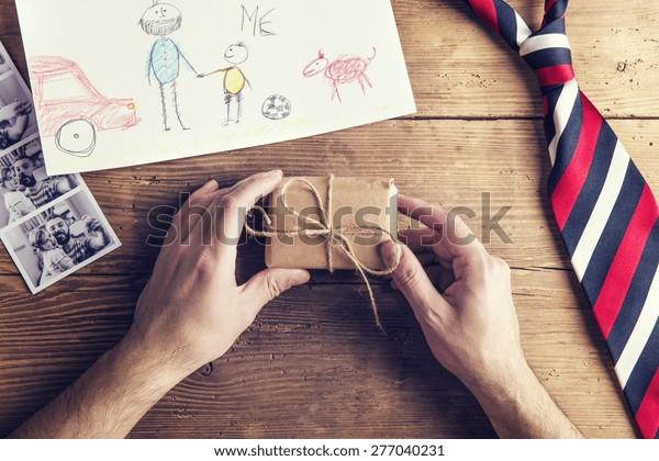 cuadros de padre e hija, niños dibujando, regalo y corbata colocados sobre el fondo del escritorio de madera.