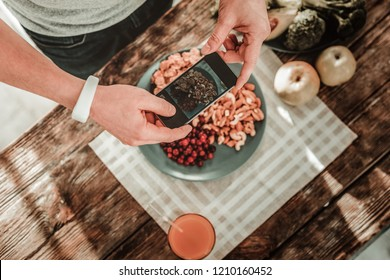 Pictures of food. Top view of a smartphone being in male hands while taking photos of food