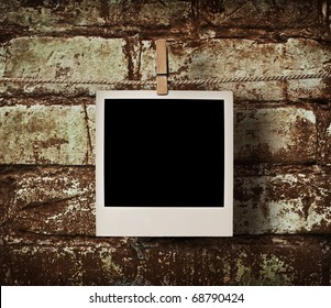 pictures on a rope with clothespins, with clipping path for images, in front of a brick wall
