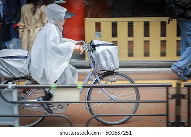 pictures of people cycling to work in the rain in city japan