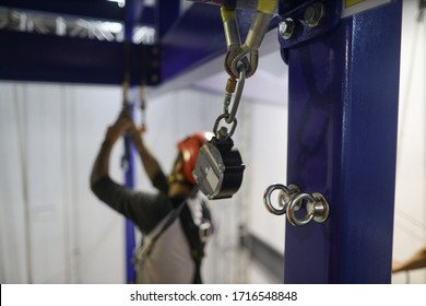 Pictures of stainless steel anchor point on structure pole with defocused abseiler using an inertia reel shock absorber lanyard as fall arrest fall restraint system while working at heights  - Shutterstock ID 1716548848