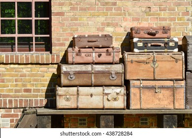 Pictures of yesteryear, old suitcases and trunks on a luggage ramp at an old train station.