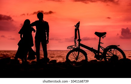 Pictures of young men and women who are watching the evening and have a bicycle on the side of the park when the red light from the evening sun splashed to see the shadow.