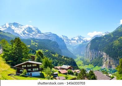 Malerisches Alpendorf Wengen, Schweiz. Berühmte Lauterbrunnen und Staubbbbachfälle im Hintergrund. Schweizer Alpen mit Schnee auf der Spitze. Die Schweiz im Sommer. Alpenlandschaft