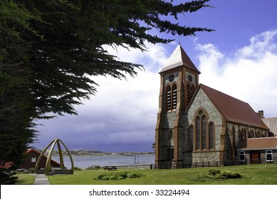 Picturesque Anglican Christ Church Cathedral, With Baleen whalebone monument at Port Stanley, Falkland Islands.
