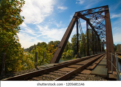 Picturesque angular view of iron and wood railroad trestle train tracks and bridge canopy, with green lush trees and vegetation, blue sky with wispy white clouds, daytime - Oregon USA