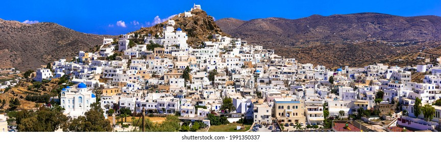 Picturesque authentic Ios island. View of scenic old town Chora with whitewashed houses and blue churches